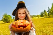pic of pirate girl  - Halloween girl in costume of a pirate holds with hands pumpkin and looks straight - JPG