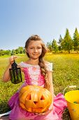 Cute girl in princess costume sits with pumpkin
