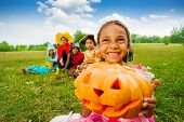 Happy African girl holds Halloween pumpkin