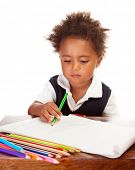Portrait of adorable sweet little black boy drawing using many colorful pencil, isolated on white ba