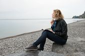 foto of poetry  - Woman writing her thoughts or poetry by the sea - JPG