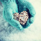 Woman hands in light teal knitted mittens are holding a beautiful heart in a snow background. Love a