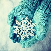 Female hands in light teal knitted mittens with sparkling wonderful snowflake on a white snow background. Winter and Christmas concept. Instagram effect.