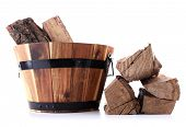 Round wooden basket full of firewood isolated on white