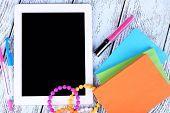 Tablet, bracelet, notebook and pen on wooden background