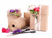 Beautiful gifts with flowers and decorative rope, isolated on white