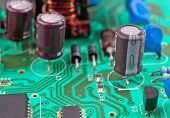 pic of transistor  - green electrical circuit board with conductors and transistors - JPG