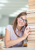 College female student on university campus with pile of books