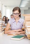 Portrait of pretty girl sitting in college library and looking at camera