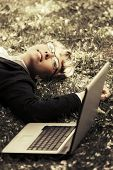 Happy business woman with laptop lying on the grass