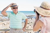 picture of take off clothes  - Happy casual woman taking photo of her partner by the coast on a sunny day - JPG