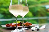 pic of french culture  - Table setting with two glasses of delicious white wine with chicken snack on background - JPG