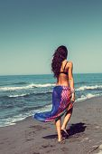barefoot young woman in colorful sarong walk on the sandy beach, back wiew, full body shot