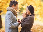 love, relationship, family and people concept - smiling couple with red gift box in autumn park
