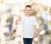 advertising, gesture, people and childhood concept - smiling boy in white blank t-shirt pointing finger himself over holidays background