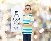vision, health, ophthalmology and people concept - smiling little boy wearing eyeglasses with eye chart over sparkling background