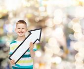advertising, direction, holidays and childhood concept - smiling little boy with white blank arrow p