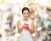 holidays, presents, wedding and happiness concept - smiling woman in white dress holding red gift bo