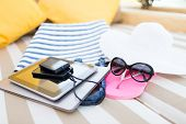 beach, summer vacation and technology concept - close up of tablet pc, notebook, smartphone and summ