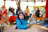 stock photo of funfair  - Adorable little boy on a carousel at Christmas funfair or market outdoors - JPG