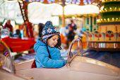Adorable Little Boy On A Carousel At Christmas Funfair Or Market