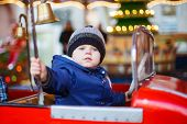 foto of funfair  - Adorable little boy on a carousel at Christmas funfair or market outdoors - JPG