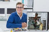 Smiling technician working on broken computer in his office