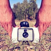 closeup of a young man taking a picture with an old instant camera, placed on the ground, with a retro effect