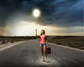 Young pretty woman tourist with suitcase walking on road