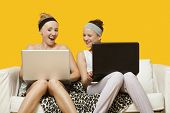 Two happy young women using laptop sitting on sofa against yellow background