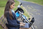 Young businesswoman using laptop while sitting on bench at park