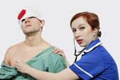 Portrait of female nurse treating an injured male patient against gray background