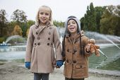 image of trench coat  - Portrait of happy brother and sister in trench coats holding hands at park - JPG