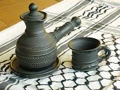 stock photo of loamy  - Ceramic coffeepot and cup on a white keffiyah scarf taken closeup - JPG
