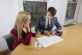 Young businessman and female colleague with paperwork at conference table