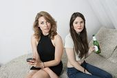 Portrait of two young women having drinks while sitting on sofa