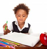 Portrait of cute little African American schoolboy sitting behind the desk and drawing, happy pupil