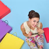 Young cheerful woman with colored paper shopping bags. Shopaholic. Shopping concept and ideas. Urban