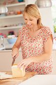 Woman Slicing Loaf Of Bread In Kitchen