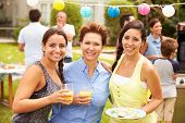 Mother With Adult Daughters Enjoying Party In Garden