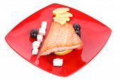 roast salmon fish meat fillet with lemon black greek olives white goat cheese on red plate isolated