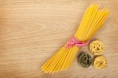 Bunch of spaghetti on wooden table background with copy space