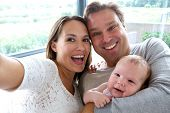 Happy Couple Taking A Selfie With Baby