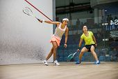 AUGUST 19, 2014 - KUALA LUMPUR, MALAYSIA: Nicol David of Malaysia (front) hits a return in her match against Liu Tsz-Ling of Hong Kong (yellow) in the CIMB Malaysian Open Squash Championship 2014.