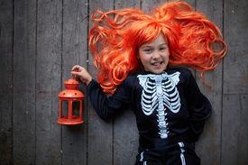 foto of antichrist  - Portrait of cute girl in red wig holding lantern - JPG