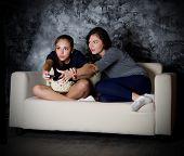 Two girls looks TV in dark room