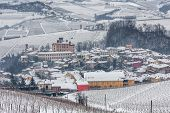 Small town of Barolo among hills of Langhe covered with snow in Piedmont, Northern Italy.
