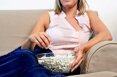 woman relaxing with a bowl of popcorn while watching t.v. on sofa couch