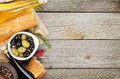 Italian food appetizer of olives, bread and spices on wooden table background with copy space