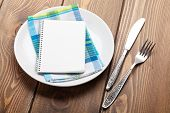 Kitchen utensils over wooden table background with notepad for copy space
